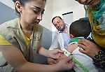 Maha Shoker, a health educator with International Orthodox Christian Charities, a member of the ACT Alliance, uses a mid-upper arm circumference (MUAC) measuring tape as she examines a Syrian refugee child in the community health center in Kab Elias, a town in Lebanon's Bekaa Valley which has filled with Syrian refugees. Dr. Akram Ziadeh looks on. Lebanon hosts some 1.5 million refugees from Syria, yet allows no large camps to be established. So refugees have moved into poor neighborhoods or established small informal settlements in border areas. International Orthodox Christian Charities provides support for the community clinic in Kab Elias, which serves many of the refugees.