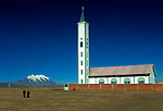 Christian church rises above two men walking toward snowcapped Mount Illimani on the Altiplano highlands in the city of El Alto, Bolivia.