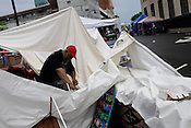 Bimbe' Cultural Arts Festival vendor David Black sorts through his canopy after a thunderstorm blew it down on top of him during the Saturday African-American music and arts festival in Durham.