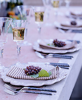Deatil of an autumnal inspired laid table with striped napkins and grapes