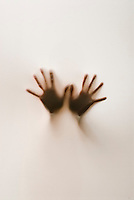 One pair of hands partially silhouetted behind translucent fabric