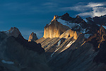 Dramatic sunset light illuminates the yellow granite face of Monte Almirante Nieto.  A cloud casts a shadow, creating a dark band across the face.  To the left are the tips of Torre Central, or Central Tower, and Torre Sur or South Tower of the Torres del Paine.  Torres del Paine National Park in Patagonia, Chile.  A UNESCO World Biosphere Reserve.  A polarizing filter was used to cut haze, increasing the contrast.