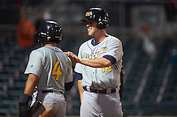 Montgomery Biscuits first baseman Casey Gillaspie (16) high fives Kean Wong (4) after scoring a run during a game against the Chattanooga Lookouts on May 2, 2016 at AT&T Field in Chattanooga, Tennessee.  Chattanooga defeated Montgomery 9-6.  (Mike Janes/Four Seam Images)