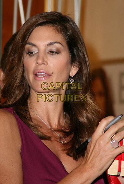 CINDY CRAWFORD .at a photocall to launch the new Omega watch collection at Westfield Shopping Centre, London, England, UK, .October 15th 2009.portrait headshot purple silver clear stone necklace earrings matching funny pen .CAP/JIL.©Jill Mayhew/Capital Pictures