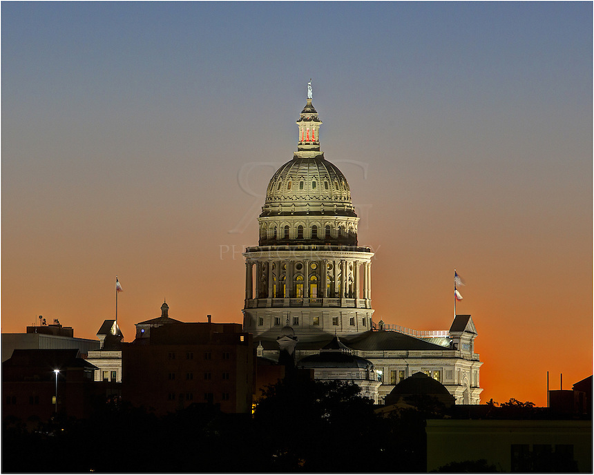 With the sky glowing orange at the break of dawn, the State Capitol of Texas slowly welcomes the first light of day over downtown Austin.