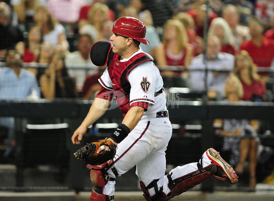 May 21, 2012; Phoenix, AZ, USA; Arizona Diamondbacks catcher Miguel Montero chases down a foul ball against the Los Angeles Dodgers in the sixth inning at Chase Field. Montero would be injured on the play. Mandatory Credit: Mark J. Rebilas-