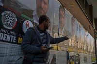 Ostia, 2 Novembre, 2017. Un immigrato nella zona del mercato di Ostia con alle spalle manifesti elettorali di Casapound.