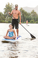 A girl enjoys a family standup paddling lesson on Wailua River, Kaua'i.