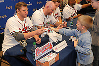 Shortstop Tyler Pastornicky of the Atlanta Braves signs a jersey for Sam Wolfe, 6, of Hendersonville, N.C., on January 27, 2012 at Academy Sports and Outdoors in Spartanburg, South Carolina. It was the first day of the 2012 Braves Country Caravan, which visits cities all across the South prior to Spring Training. (Tom Priddy/Four Seam Images)