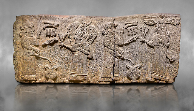 Aslantepe Monumental Hittite relief sculpted orthostat stone panel.  Limestone, Aslantepe, Malatya, 1200-700 B.C. <br /> Scene of the king's offering drink and sacrifice to the gods. The king offers to the winged god of the moon who stands across and holds a lightning bundle in his hand. Behind the king is the queen, who also offers to goddess of the sun holding a sceptre in his hand. King's left hand is in a position to worship. <br /> <br /> Against a grey art background.