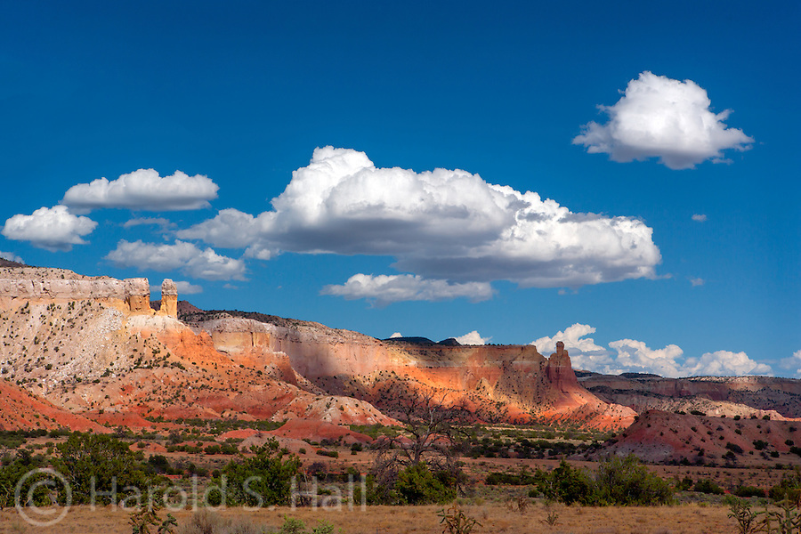 This is Georgia O'Keeffe country in Abiquiu, New Mexico.  The red cliffs, vivid blue sky and puffy cumulus clouds is what has drawn visitors to northern New Mexico for years.