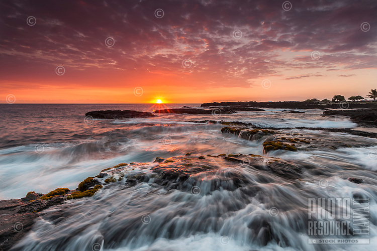 The sun sets in a purple and orange sky over rushing ocean water along the Kona Coast of the Big Island of Hawai'i.