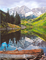 The Maroon Bells reflect in calm Maroon Lake on a cloudy morning, near Aspen, Colorado