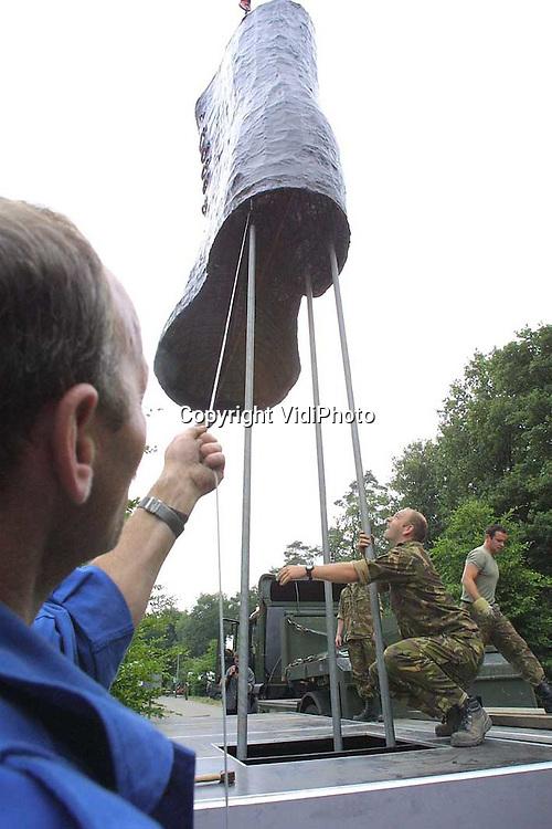 Foto: VidiPhoto..NIJMEGEN - Op recreatieterrein Heumensoord in Nijmegen wordt door militairen van de Koninklijke Landmacht de laatste hand gelegd aan een kamp voor zo'n 6500 militairen uit de hele wereld. De soldaten doen mee aan de Nijmeegse Vierdaagse, die volgende week dinsdag van start gaat. Het opbouwen en afbreken van kamp Heumensoord duurt in totaal tien weken en kost Defensie meer dan 1 miljoen gulden. Aan de Nijmeegse nemen meer dan 40.000 wandelaars deel. Foto: Het plaatsen van reuzen soldatenlaarzen, als onderdeel van de poort.