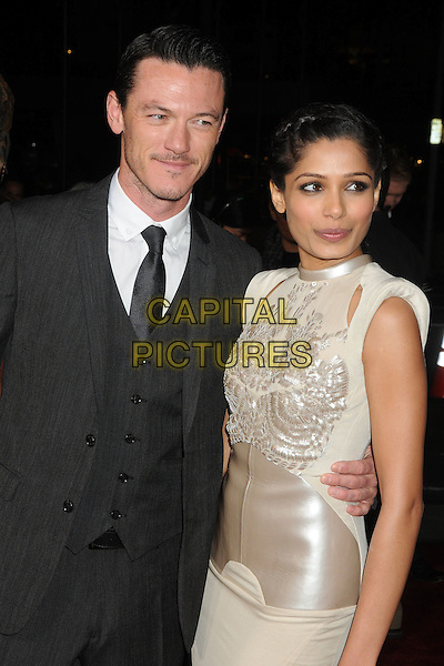 Luke Evans & Freida Pinto (wearing Antoni Berardi).The World Premiere of 'Immortals' held at The Nokia Theater Live in Los Angeles, California, USA..November 7th, 2011.half length white blush cut out shoulders embroidered detail bodice dress satin panel black grey gray suit waistcoat .CAP/ADM/BP.©Byron Purvis/AdMedia/Capital Pictures.