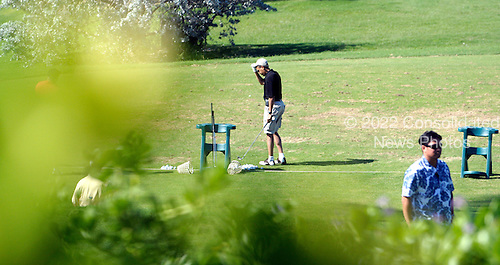 Kailua, Hawaii - December 24, 2008 -- United States President-elect Barack Obama adjusts his hat between hitting golf balls on the windy driving range at Mid-Pacific Country Club in Kailua, Hawaii on Wednesday, December 24, 2008..Credit: Joaquin Siopack / Pool via CNP