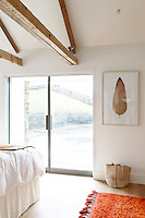 Sliding glass doors in the master bedroom open onto a balcony with a glass balustrade overlooking the estuary