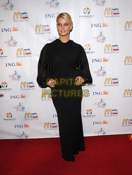 JESSICA SIMPSON.attends Noche de Ninos Gala benefiting Children's Hospital of Los Angeles held at The Beverly Hilton Hotel, .Beverly Hills, California, USA, October 7th 2006. .full length black dress hand on hip peep hole sheer sleeves  long .Ref: DVS.www.capitalpictures.com.sales@capitalpictures.com.©Debbie VanStory/Capital Pictures