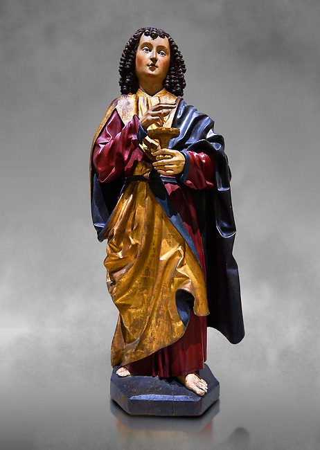 Gothic wooden statue of Sant Joan Evangelista (John the Evangelist) from Gremany, circa 1500, tempera and gold leaf on wood.  National Museum of Catalan Art, Barcelona, Spain, inv no: MNAC  64114. Against a grey textured background.