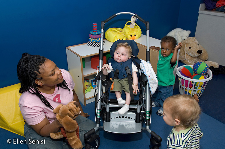 MR / Schenectady, NY.Schenectady Day Nursery / private non-profit daycare center / Infant Class.Caregiver (African-American) wity puppet and infants gather around and interact with infant. (boy, 1, cerebral palsy) - (Child is sitting in pediatric stroller - style manual wheelchair).MR: Did1, AF-SDNI.© Ellen B. Senisi