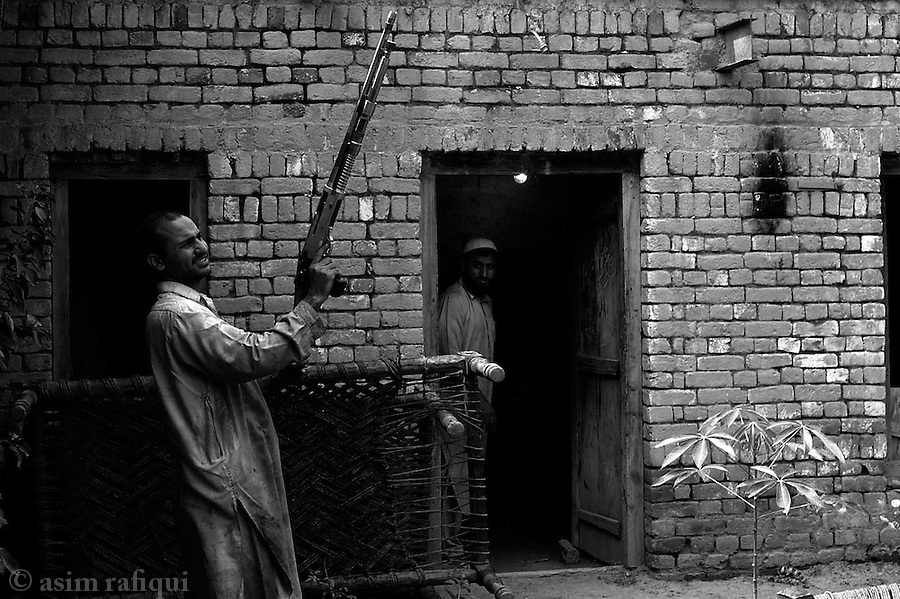 completed weapons are test fired in the main compound of the gun factory.  throughout the day the entire town rings with the sounds of weapons being tested by manufacturers and buyers alike.  testing is done in open compounds and on the main streets of the town.  darra adam khel, tribal areas, pakistan.  september 200&amp;#xA;&amp;#xA;copyright asim rafiqui 2003<br />