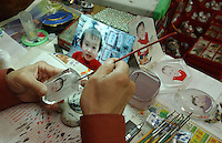 Chinese craftsmen carve and paint images of Chinese girls being adopted for their new parents in Guangzhou, China.  Around 10,000 babies are adopted from China annually.