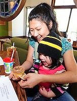 Gena Lindholm (back) and Madeline Lingk enjoy a cupcake at Daisy Cafe in Madison