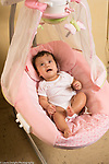 4 month old baby girl in infant seat with mobile looking frightened or unhappy