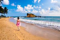 Tourist walking along Mirissa Beach, South Coast of Sri Lanka, Asia. This is a photo of a tourist walking along Mirissa Beach, Sri Lanka, Asia. Mirissa Beach is a popular sandy tourist beach on the South Coast of Sri Lanka.