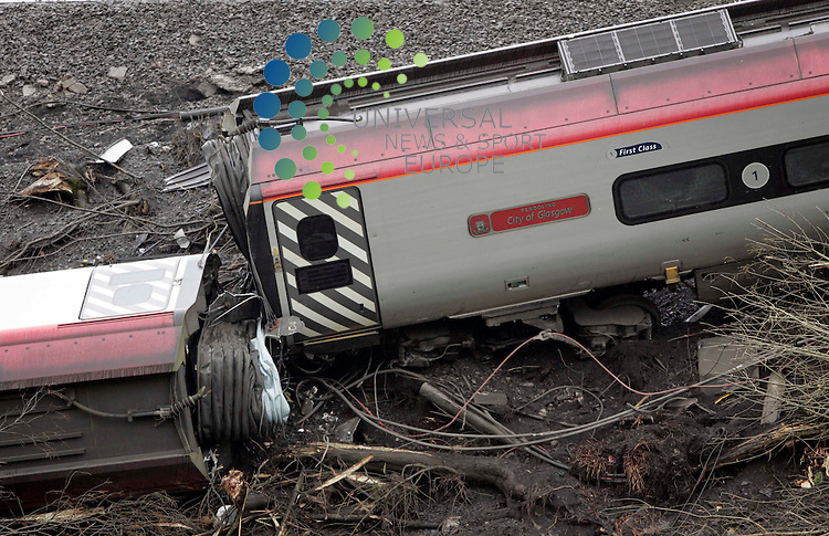 "Rail inspectors pass a dedicated "" City Of Glasgow"" wrecked carriage after elderly a woman has died and five other passengers have been seriously hurt in a train derailment in Cumbria. Several carriages were left on their side after the 1715 Virgin train from London to Glasgow Central crashed at Grayrigg, near Kendal, at 2015 GMT..Maurice McDonald Universal News/Photo..."