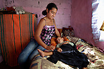 Feride Ramadan covers her one-year old son Birdzhan in their house in the Maxsuda neighborhood of Varna, Bulgaria. They are Turkish-speaking Roma, and were violently driven out of one neighborhood by racist gangs. They took refuge in a United Methodist Church for a year before finding this small house to rent.