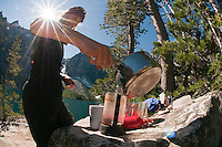 Backpacker pouring water from pot into camping coffee pot at camp on Colchuck Lake, Alpine Lakes Wilderness, WA.