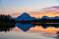 The summer sun sets behind Mt. Moran and Oxbow Bend in Grand Teton National Park, Wyoming.