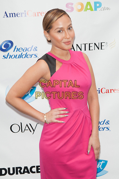Adrienne Bailon <br /> attends the 'Swim for Relief' Benefiting Hurricane Sandy Recovery at Herald Square, New York City, NY., USA.<br /> October 9th, 2013 <br /> half length dress hand on hip pink<br /> CAP/MPI/COR<br /> &copy;Corredor99/ MediaPunch/Capital Pictures