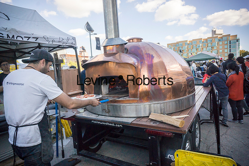 A worker from Big Mozz prepares pizza in Smorgasburg in East River State Park in the Williamsburg neighborhood of Brooklyn in New York on Saturday, October 15, 2016. The marketplace features prepared and artisanal foods made in Brooklyn by small entrepreneurs. (© Richard B. Levine)