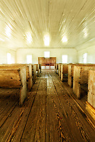 Inside of simple church in Hyde County near Lake Mattamuskeet with wood floors and pews and light pouring in windows