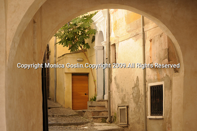 An archway showing a building with a white doorway and a small tree in front of it in Castello, a town in the mountains on Lake Lugano, Italy.