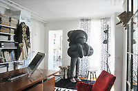 "In the office a ""Bubble"" sculpture by Daniel Firman stands next to the French windows with a pair of stools imaginatively created out of piles of old catalogues and two checked cushions"