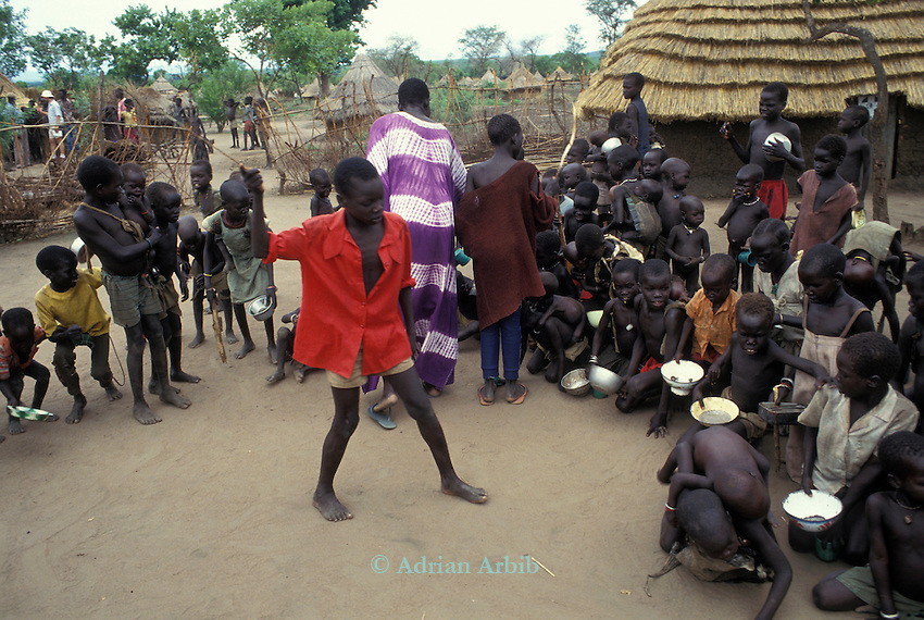 A Dinka boy beats other children into place at a feeding  station for  Southern Sudanese  Dinka  displaced  by the war in South Sudan.