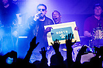 """© Joel Goodman - 07973 332324 . 11/04/2015 . Manchester , UK . Shaun Ryder and Kermit ( Paul Leveridge ) holding a framed """" North """" . Black Grape perform a reunion gig in support of Bez's Reality Party at the Old Granada Studios Warehouse . Photo credit : Joel Goodman"""