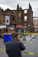 A man talks on a mobile phone as he looks out over a cordoned area and damaged buildings where rioting took place two nights earlier in Tottenham, London borough of Haringey. London saw the beginnings of riots on Saturday evening, after a peaceful protest in response to the shooting by police of Mark Duggan during an attempted arrest, escalated into violence. By the third night of violence, rioting had spread to many areas of the capital and to other cities around the country.