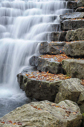 Waterfall flowing over large evenly spaced rock stairs of a dam breast, Johns Mill Run Dam in the fall, Laurel Run State Park, Somerset, Pennsylvania.