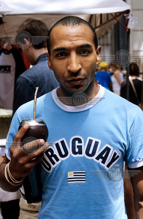 A man wearing a 'Uruguay' t-shirt drinks traditional mate tea from a typical calabash gourd with a bombilla straw.