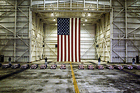 Dover, Delawre, USA, Octobere 29, 1983<br /> At precisely 7 A.M., a Marine honor guard and a color guard in ceremonial dress uniforms marched into a huge hangar at the Dover Air Force Base and stood facing 16 coffins. Behind them, suspended from the beams of the hangar, was a 38-foot American flag.<br /> The ceremony was the first on American soil honoring servicemen killed in the bombing in Beirut and the invasion of Grenada. Credit: Mark Reinstein/MediaPunch
