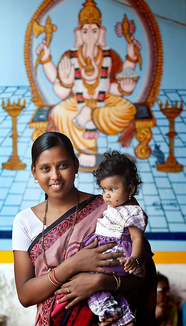 21 May 2013, Rattgeri Village, Karnartaka, India:  Shilpa Pakirappa Gunjab with baby Saraswati  waits to be attended to by Dr Bellada of the Karnataka Mobile Health Clinic project in the Anganwadi centre at Rattgeri  Village outside of Hubli. The World Bank is financing the Karnataka Health Systems Project that is bringing mobile health clinics to remote villages in Karnataka and covers the cost of an ambulance, a doctor, pharmacist, two nurses, a cleaner and a driver. Villagers have the opportunity to see a doctor once a week for basic services and will be referred to Primary Health Care centres for larger issues Picture by Graham Crouch/World Bank