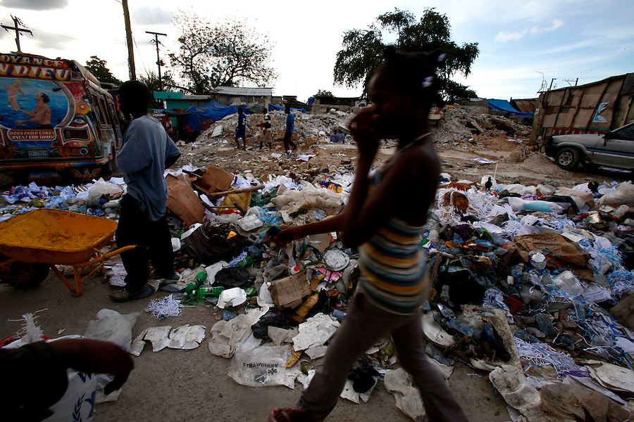 Nov 10, 2010 - Port-au-Prince, Haiti.Residents walk by large piles of trash along the road in Port-au-Prince, Haiti on Wednesday, November 10, 2010 as fears of a Cholera outbreak spread through the area just two days after cases of the infection were confirmed in the Haitian capital. Officials from the Pan American Health Organization warn that Haiti's cholera epidemic, spread primarily through consuming infected water and food, is likely to grow much larger in the wake of Hurricane Tomas.  (Credit Image: Brian Blanco/ZUMA Press)