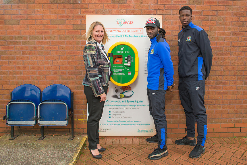 Samantha Sheehan, Executive Director of BMI Healthcare's Beardwood Hospital (left) at a ceremony with Blackburn Rovers FC players Marvin Emnes (centre) and Lucas João (right) marking the sponsorship of a Defibrillator unit by BMI Healthcare at Ewood Park, home of Blackburn Rovers FC.