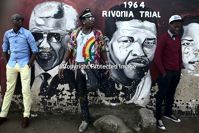 SOWETO, SOUTH AFRICA MAY 26: Sibu FDB, (c) a young designer part of the collective group Smarteez with colleagues in front of Mandela murals on May 26, 2012 close to Regina Mundi church in Soweto, South Africa. Known for their street style fashion they had a great opportunity recently to show their township inspired designs at South African fashion week. Soweto today is a mix of old housing and newly constructed townhouses. The population in Soweto is estimated to be around one million people. A new hungry black middle-class is growing steadily. Many residents work in Johannesburg but the last years many shopping malls have been built, and people are starting to spend their money in Soweto. (Photo by: Per-Anders Pettersson)