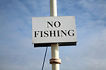 No fishing sign against blue sky