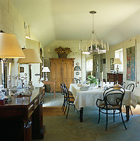 Summer dinners are held in the big hall, a billiard table doubling as a dining table, with an octagonal chandelier hanging from the ceiling and walls of natural lime plaster cut to look like stone blocks